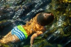 Pojke som simmar undervattens- härlig sikt av kristallklart genomskinligt vatten av havet royaltyfri foto