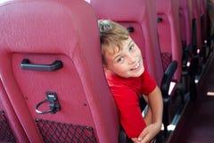Pojke som sitter i bussfåtölj Arkivfoto