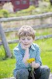 Pojke som sitter på bänk med buketten av nya valda blommor royaltyfri foto