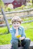 Pojke som sitter p? b?nk med buketten av nya valda blommor fotografering för bildbyråer
