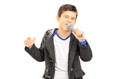 Pojke som sjunger på mikrofonen Arkivbild