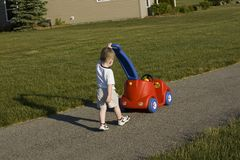 pojke som skjuter toybarn Arkivbild
