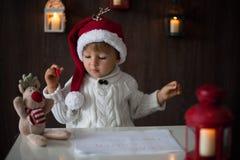 Pojke som skriver till jultomten Arkivbild