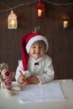 Pojke som skriver till jultomten Royaltyfri Bild