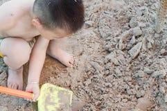 Pojke som skyfflar sander Arkivfoton