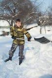 Pojke som skyfflar snö från gångbanan Royaltyfria Bilder
