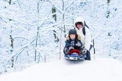 Pojke som sledding ner kullen med hans fader som hjälper honom Royaltyfria Foton