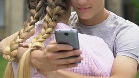 Pojke som smsar på smartphonen, medan omfamna flickvännen, lögnen och sveket, closeup lager videofilmer