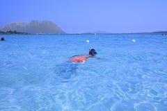Pojke som snorklar på en härlig strand arkivfoto
