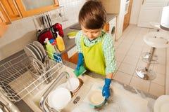 Pojke som snyltar bunkar under rinnande vatten i vasken Arkivfoto