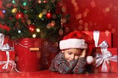Pojke som sover bredvid julgranen, arkivbild