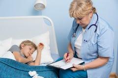 Pojke som sover i sjukhussäng Arkivfoto