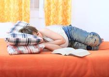 Pojke som sover med en bok Royaltyfri Bild