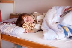 Pojke som sover på britssäng Royaltyfria Bilder