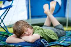 Pojke som sover på sovsäcken med tältet i bakgrund Royaltyfri Foto