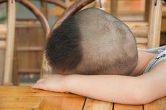 Pojke som sover på tabellen Arkivfoto