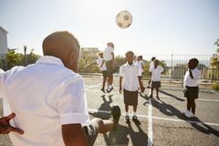 Pojke som sparkar bollen till klasskompisar i grundskolalekplats royaltyfri foto