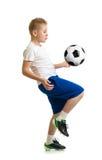 Pojke som sparkar fotbollbollen vid det isolerade knäet arkivbilder