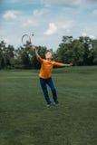 Pojke som spelar badminton med racket och fjäderboll, på grönt fält arkivbilder