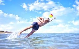 Pojke som spelar bollen i havet Arkivbilder