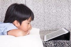 Pojke som spelar den digitala minnestavlan Royaltyfri Foto