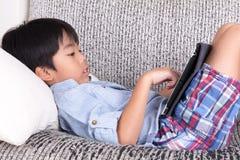 Pojke som spelar den digitala minnestavlan Royaltyfri Fotografi
