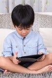 Pojke som spelar den digitala minnestavlan Arkivfoto