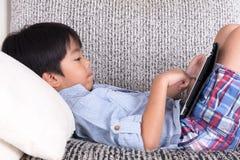 Pojke som spelar den digitala minnestavlan Royaltyfria Foton
