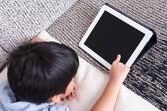 Pojke som spelar den digitala minnestavlan Arkivfoton