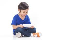 Pojke som spelar en lek på datorminnestavlan Arkivbild
