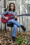 Pojke som spelar en röd gitarr Royaltyfri Bild