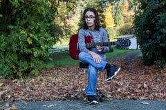 Pojke som spelar en röd gitarr Arkivfoton