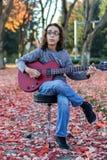 Pojke som spelar en röd gitarr Arkivbilder