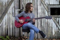 Pojke som spelar en röd gitarr Arkivfoto