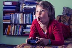 Pojke som spelar en videospelkonsol Fotografering för Bildbyråer