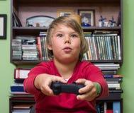 Pojke som spelar en videospelkonsol Arkivbild