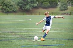 Pojke som spelar fotboll - sparka bollen arkivfoto