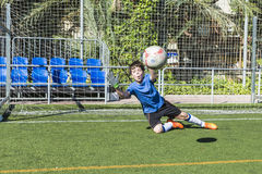 Pojke som spelar fotbollgoalien Fotografering för Bildbyråer