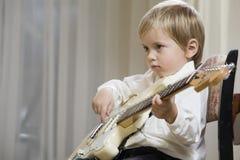 Pojke som spelar gitarren Arkivfoto