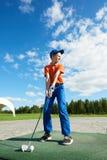 Pojke som spelar golf på fältet i sommar royaltyfri foto