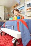Pojke som spelar i barnkammare i säng Royaltyfri Foto