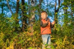 Pojke som spelar i höstskogen Royaltyfria Foton