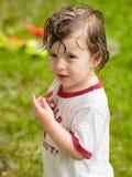 Pojke som spelar i regnet Arkivbild