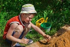Pojke som spelar i sandlådan på lekplatsen arkivbild