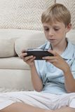 Pojke som spelar lekar på PSP Royaltyfri Fotografi