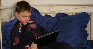Pojke som spelar leken på minnestavlan, medan ligga på säng stock video