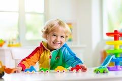 Pojke som spelar leksakbilar Unge med leksaker barn och bil royaltyfria foton