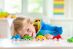 Pojke som spelar leksakbilar Unge med leksaker barn och bil arkivfoto