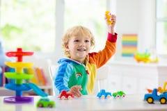 Pojke som spelar leksakbilar Unge med leksaker barn och bil royaltyfri bild