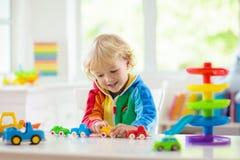 Pojke som spelar leksakbilar Unge med leksaker barn och bil royaltyfria bilder
